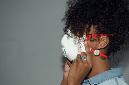 Profile of a black woman wearing a FFP3 mask with an exhalation valve. Coronavirus. Protection.  Cop...