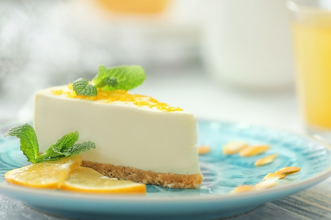 Tasty cheesecake slice with lemons on plate
