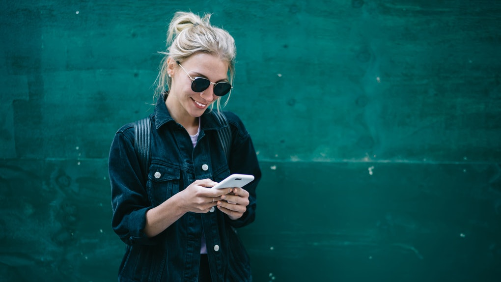 A happy woman looks down at phone while texting in front of green wall outside.
