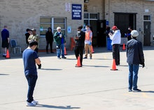 Voters stand apart as they wait in line to cast ballots in the Wisconsin presidential primary electi...