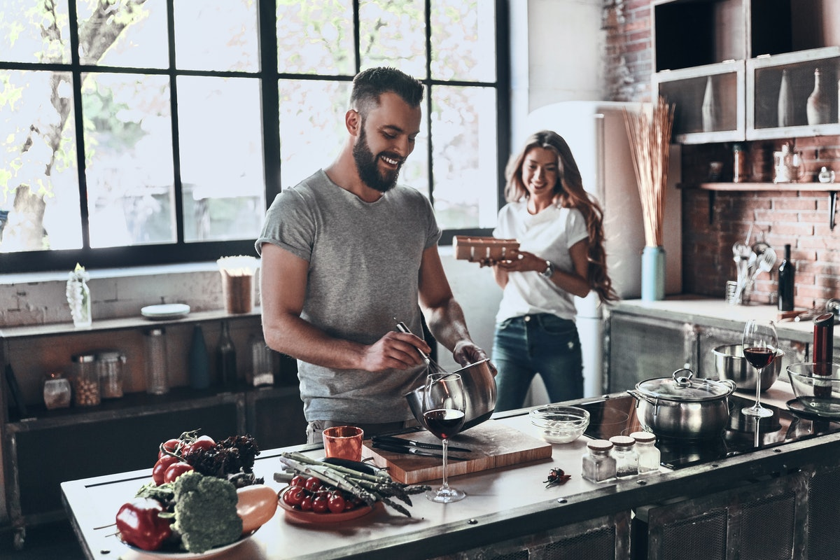 A young, happy couple enjoys wine and prepares a meal in their sunny kitchen.