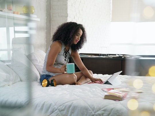 African american college student doing homework in bed at home, young black woman preparing school test in bedroom with laptop pc