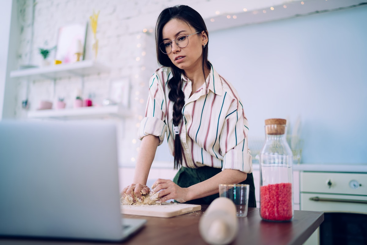 Charming black haired woman in striped shirt and glasses kneading dough while watching food recipe t...