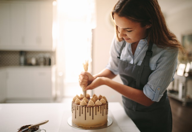 Woman decorating chocolate cake in the kitchen. Female chef making a cake at home.