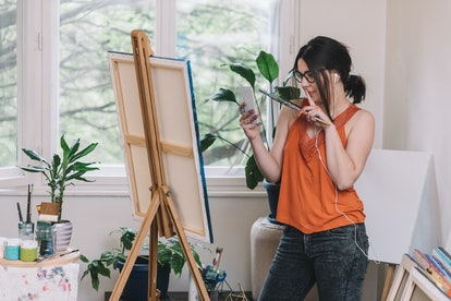 Young female artist taking a photo of her painting with smart phone