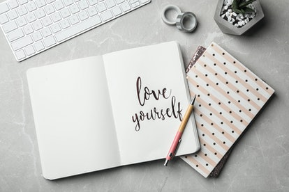 Flat lay composition with words LOVE YOURSELF written in notebook on grey table