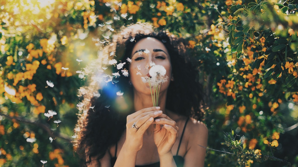 A woman with brown curly hair blows out a dandelion in front of orange flower bushes on a sunny day.