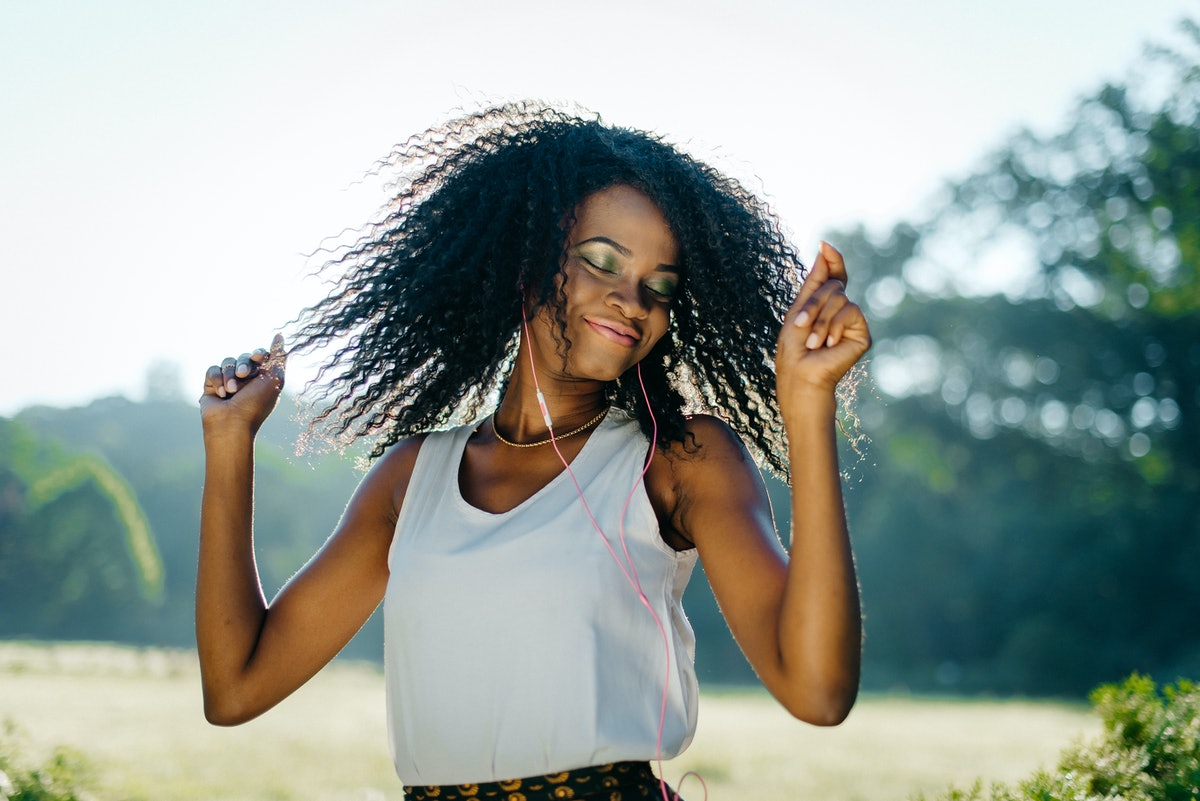 Emotional outdoor portrait. The charming young african girl with pretty smile and green eye shadows is shaking her curly hair while listening to music in her eyephones.