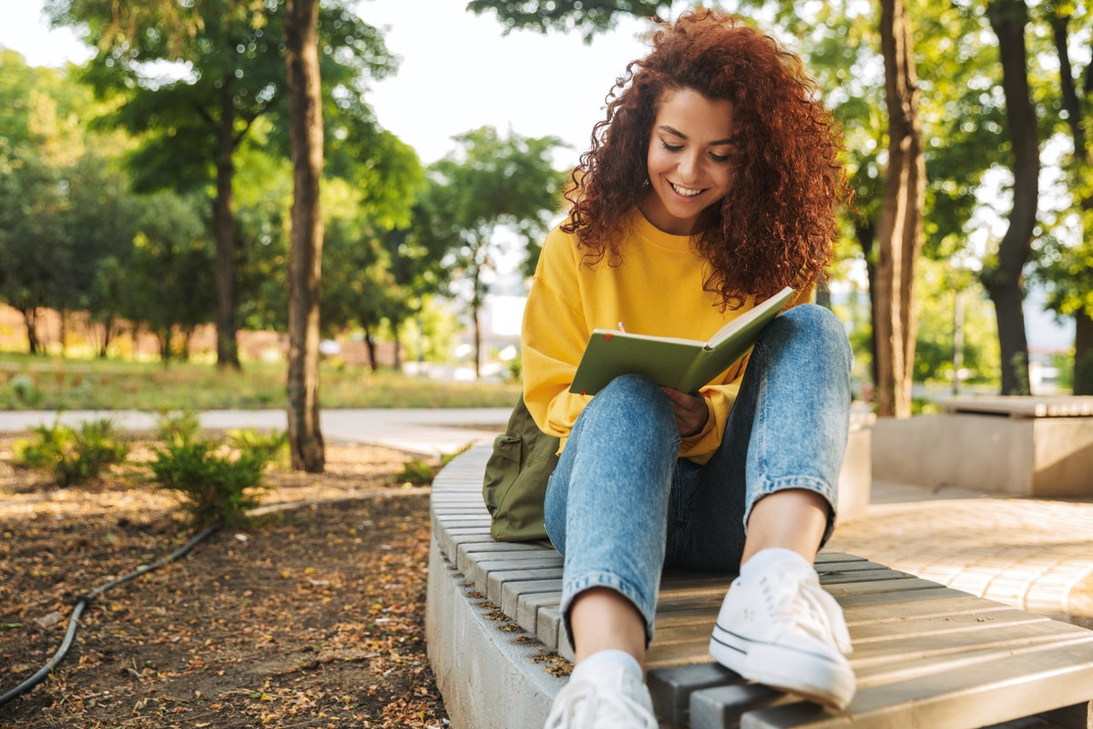 A girl reads a book in the park outside.