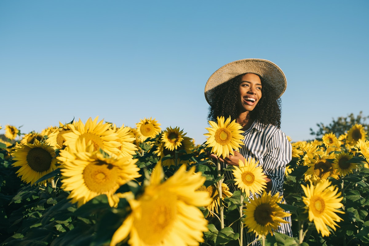 Happy young black woman in a sunflower field