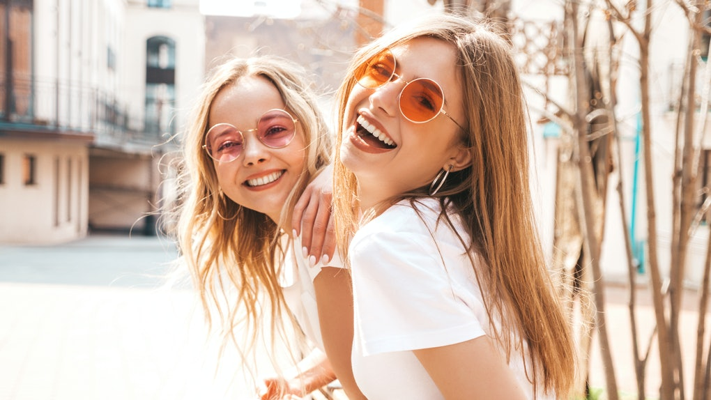 Two young women in white T-shirts and colorful sunglasses smile outside on a sunny day.