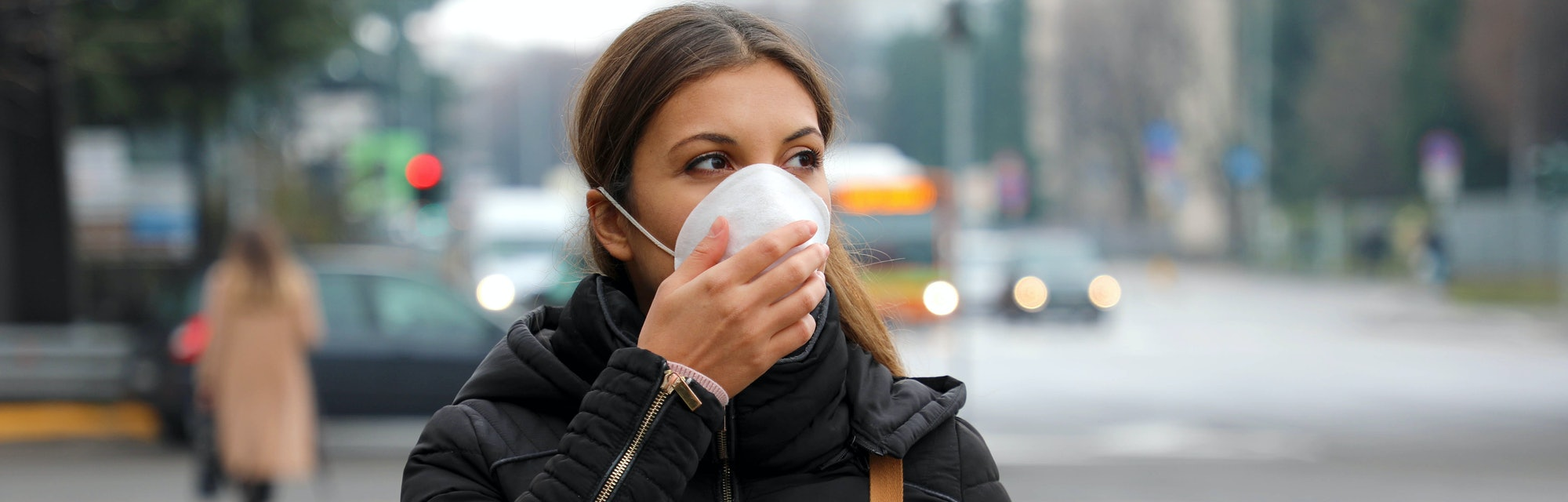 COVID-19 Pandemic Coronavirus Woman in city street wearing face mask protective for spreading of dis...