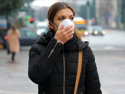 COVID-19 Pandemic Coronavirus Woman in city street wearing face mask protective for spreading of disease virus SARS-CoV-2. Girl with protective mask on face against Coronavirus Disease 2019.