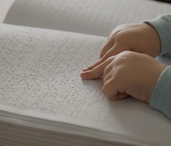 Blind child reading book written in Braille, closeup