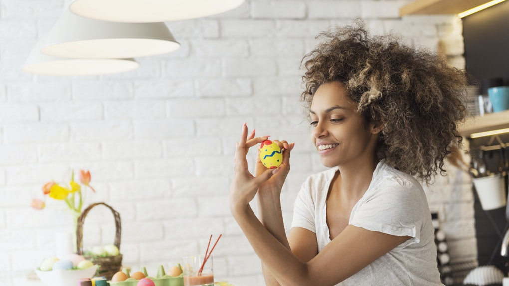 A woman in a white T-shirt smiles at her kitchen table while holding up a yellow Easter egg she painted.