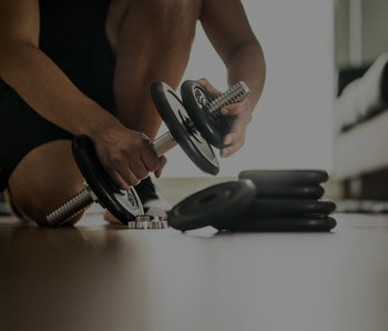 Improvement and getting stronger in fitness, exercise and muscle training concept. Man adding more weight to adjustable dumbbell in home gym. Dedication, motivation and progression.