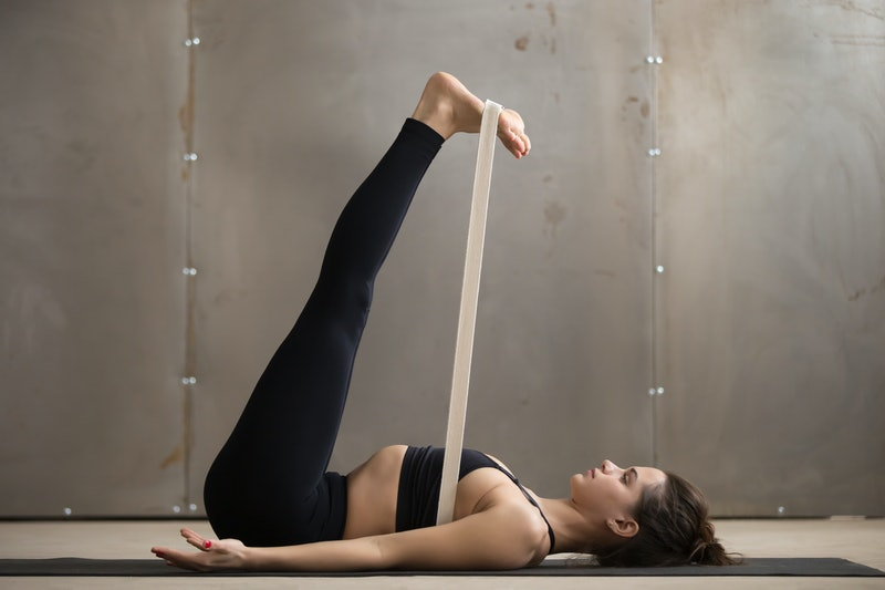 Young woman in black practicing yoga, stretching in Double Leg Lift, Urdhva Prasarita Padasana exercise using strap, Upward Extended Feet pose, working out, cool urban style, full length, grey studio