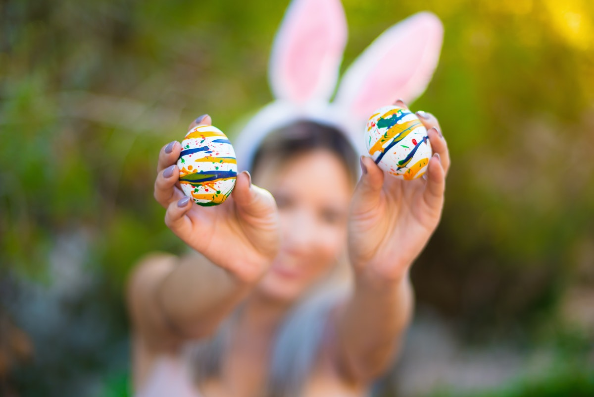 Young woman wearing bunny ears holds up two decorated Easter eggs.