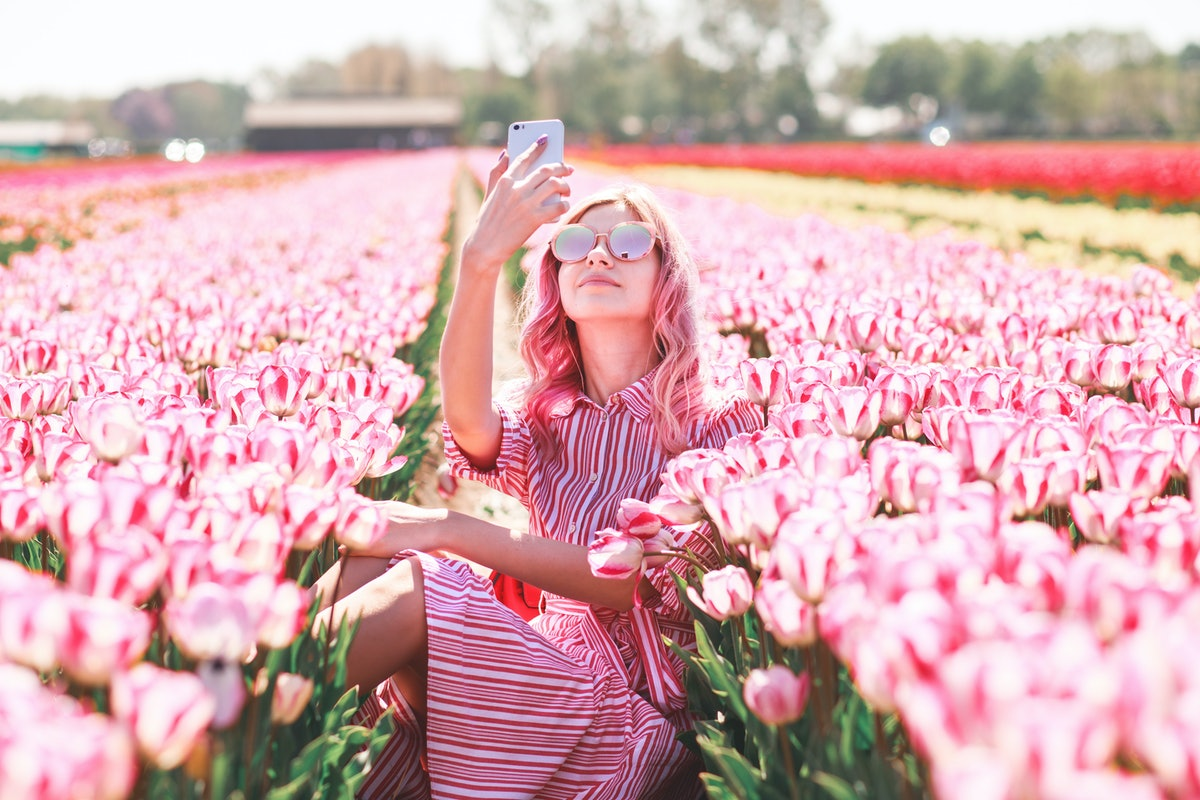 A woman in a pink striped dress and pink sunglasses takes a selfie in a field of pink tulips.