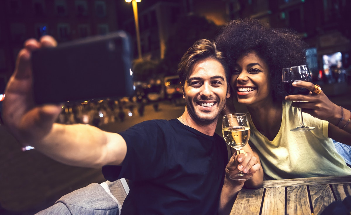 A young couple sits at a picnic table and holds up their wine glasses for a selfie.