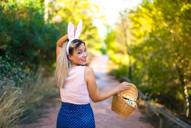 A woman walks down a trail with bunny ears on and holding a basket of Easter eggs.
