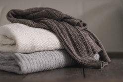 Stack of neatly folded woolen knitwear. Minimal lifestyle, capsule wardrobe. Autumn-winter men fashi...