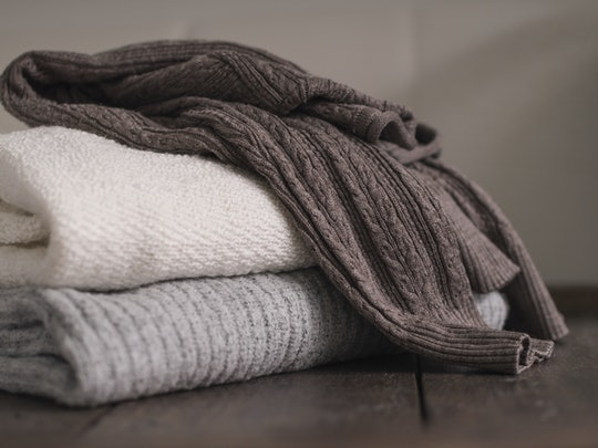 Stack of neatly folded woolen knitwear. Minimal lifestyle, capsule wardrobe. Autumn-winter men fashion wardrobe concept. Earth tones, horizontal copy space
