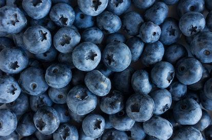 Fresh Blueberry Background. Texture blueberry berries close up. Sprinkle blueberries. Ripe blueberri...