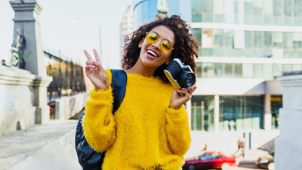 A happy woman, wearing a fuzzy yellow sweater and sunglasses throws up a peace sign while holding her camera.