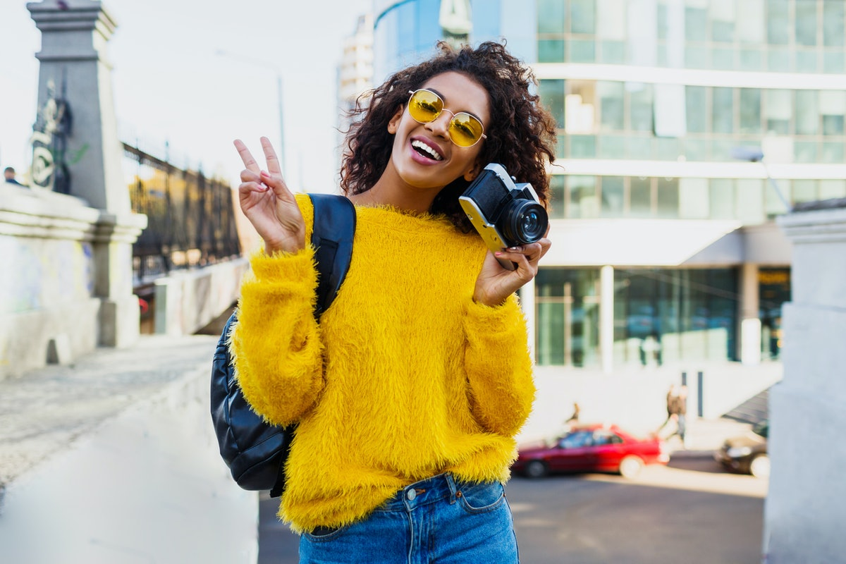 A happy woman, wearing a fuzzy yellow sweater and sunglasses throws up a peace sign while holding he...