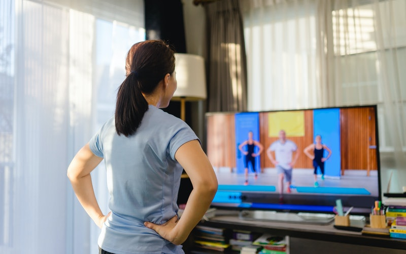 A person stands with their hands on their hips, facing away from the camera to watch three exercise instructors on their TV. Getting bored with your workouts is very normal, but that doesn't mean you have to throw in the towel.