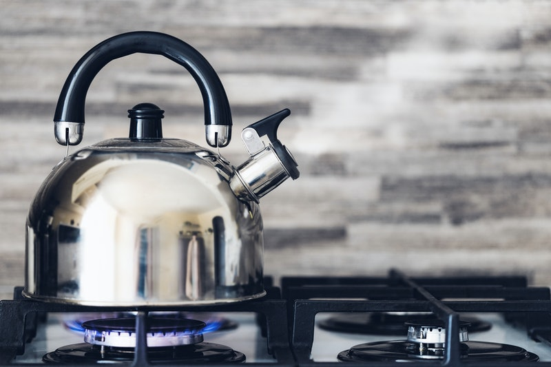 A metal silver teapot on a gas stove in the kitchen