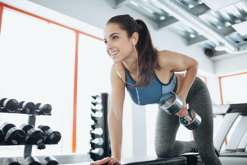 Young beautiful woman doing exercises with dumbbell in gym. Glad smiling girl is enjoying with her training process. She is working hard
