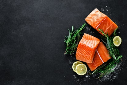 Salmon. Fresh raw salmon fish fillet with cooking ingredients, herbs and lemon on black background, ...