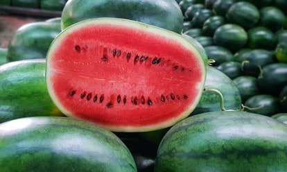 Many big sweet green watermelons and one cut watermelon.Young green watermelon.Watermelon slice.Many...