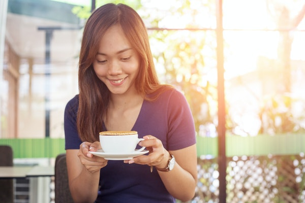 A happy woman holds a cup of coffee with a stroopwafel on top, while sitting in an outdoor cafe.