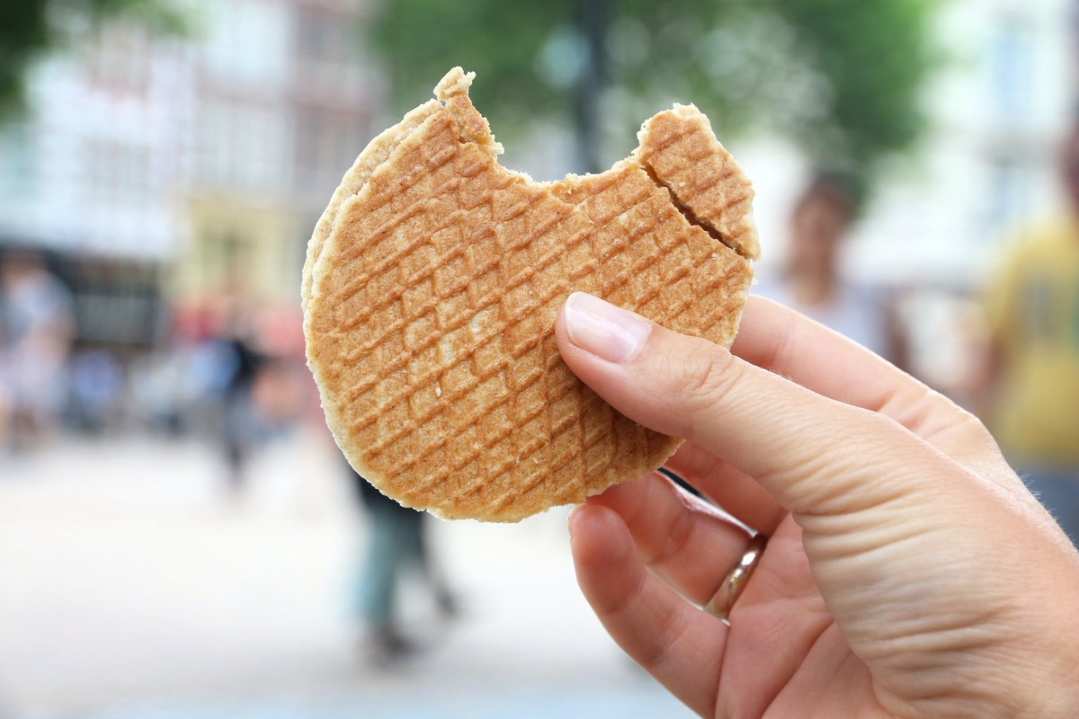 A woman's hand holds up a stroopwafel with a bite taken out of it.