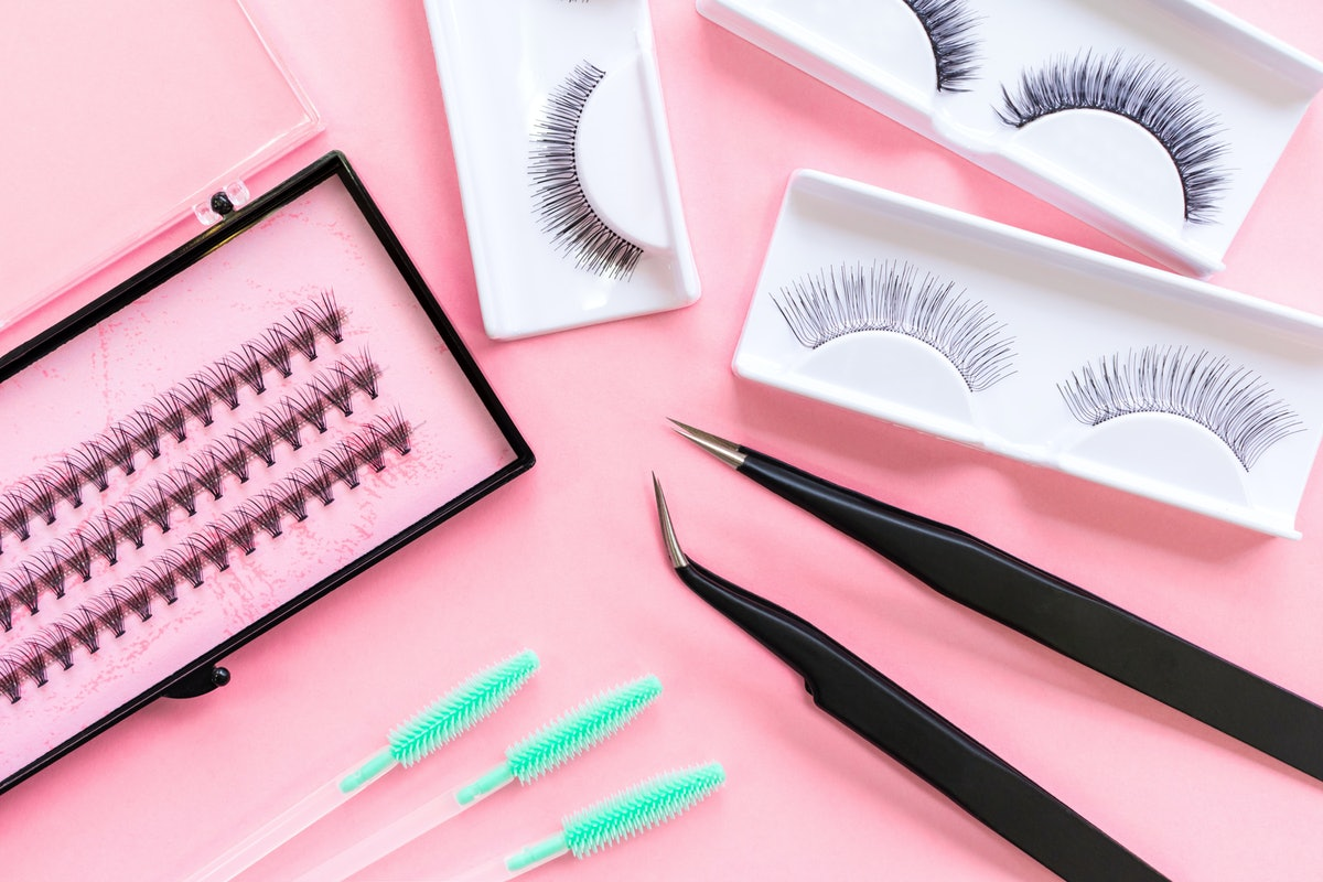 Tools for eyelash extension on trendy pastel pink background. False eyelashes, tweezers and brushes. Beauty shop. Makeup cosmetics. Top view, flat lay.
