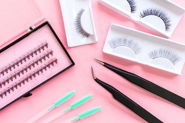 Tools for eyelash extension on trendy pastel pink background. False eyelashes, tweezers and brushes....
