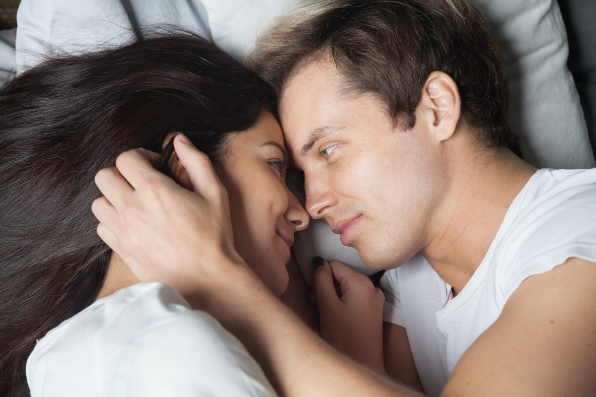 Happy loving couple relaxing on bed at home, young man touching smiling beautiful woman face, looking in the eyes stroking caressing, enjoying togetherness and tenderness in love, top close up view