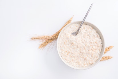Healthy food classic porridge in white bowl on background. oatmeal food breakfast. Top view.