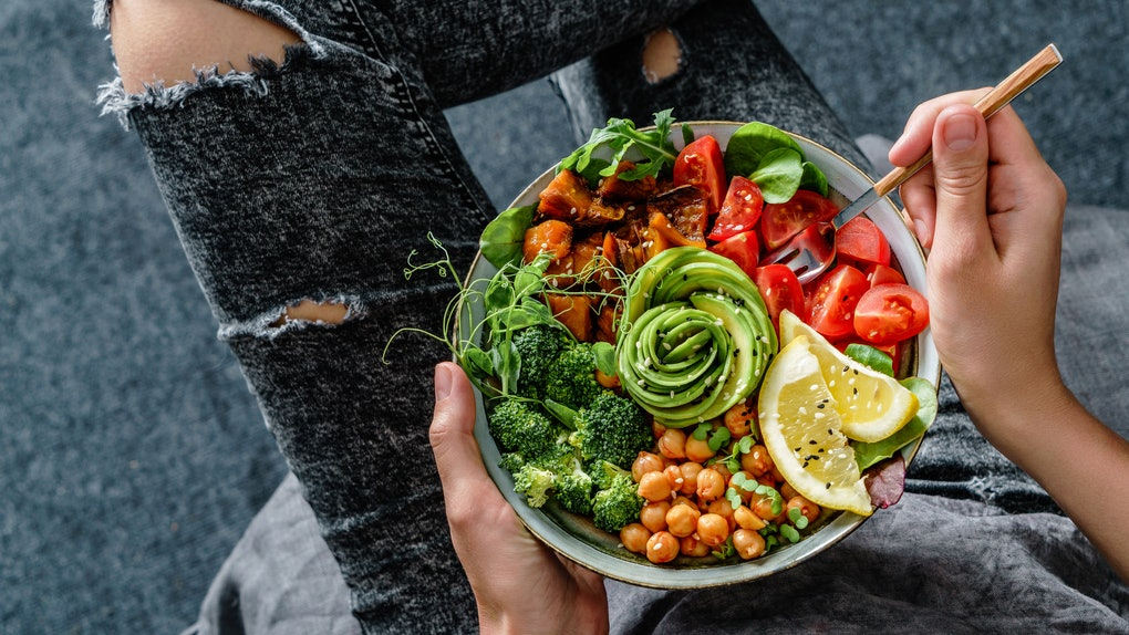 A woman in distressed gray jeans holds a colorful bowl of salad, veggies, and an avocado that's cut like a rose on her lap.