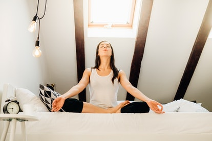 Woman meditating in bedroom at home.Antistress practice.Overcoming anxiety and fear.Mindfullness meditation.Breathing exercise.Peaceful and calm mind.Quarantined at home activities.Mental health.Zen