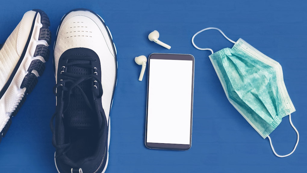 Jogging and healthy life concept during Coronavirus pandemic quarantine – safety measures for runners with medical mask next to sport shoes and mobile phone with wireless earphones