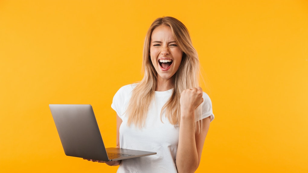 Portrait of an excited young blonde girl holding laptop computer and celebrating success isolated over yellow background