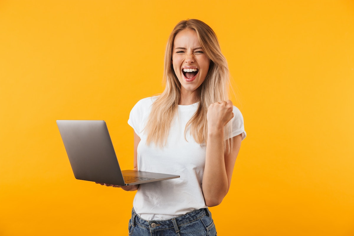 Portrait of an excited young blonde girl holding laptop computer and celebrating success isolated ov...