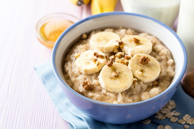 Oatmeal porridge with banana, walnuts and honey in bowl on purple wooden background. Healthy breakfast. Selective focus.