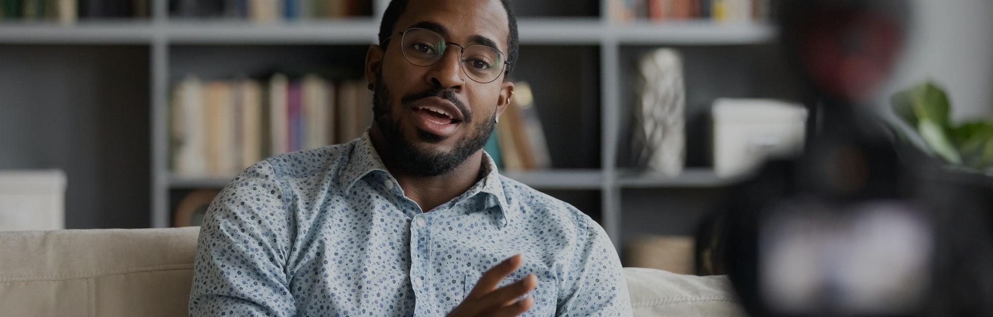Millennial african hipster man blogger recording vlog on digital camera sit on sofa in living room, ...