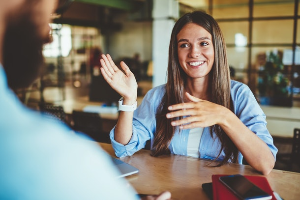 Happy successful hipster girl explaining information to male friend sitting in front, positive man and woman talking and discussing ideas for new startup project at spending time in coworking space