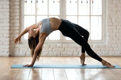Young sporty yogi woman practicing yoga, doing Wild Thing, Flip-the-Dog exercise, Camatkarasana pose, working out, wearing sportswear, black pants and top, indoor full length, white yoga studio